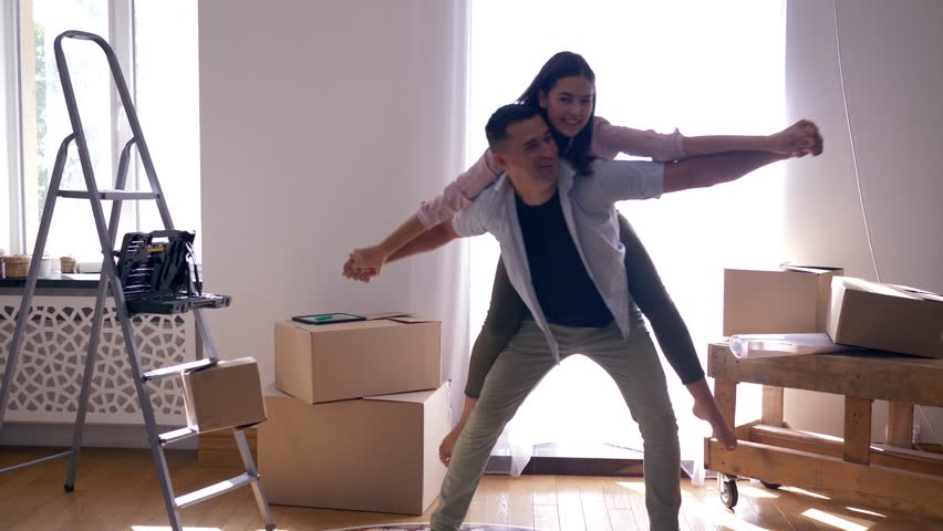 Relocation to new housing, joy pair is laughing and guy is Carrying girl on back among boxes during moving to new apartment | Shutterstock HD Video #1016251912