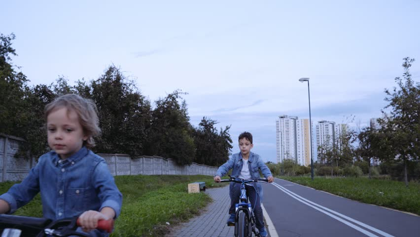 Two caucasian boys in denim clothes ride bicycle. | Shutterstock HD Video #1016287672