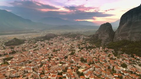 Aerial shot magnificent small European city or suburb Kalambaka near mountain Meteora at sunset flying over great landscape amazing colored sky with sunbeams and clouds