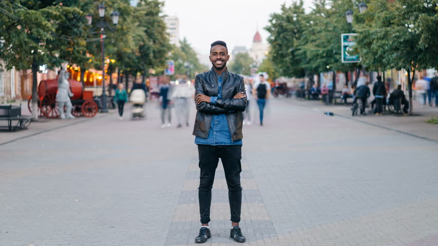 Time-lapse portrait of cheerful African American man standing in city center wearing stylish clothes looking at camera and smiling while people are passing by. | Shutterstock HD Video #1016310262