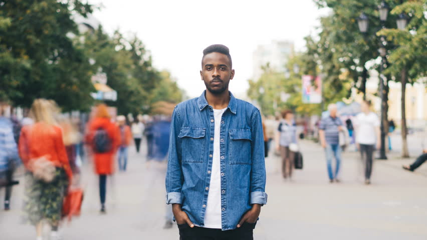 Time-lapse portrait of African American man in casual clothes looking at camera standing in busy street downtown suffering from loneliness when people are passing by. | Shutterstock HD Video #1016312962