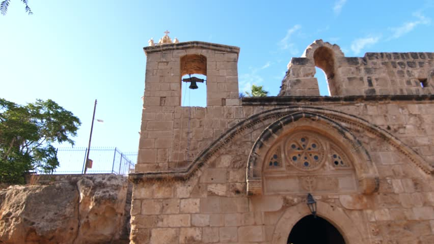 Temple with tall bell tower. View of ancient temple with belfries in slow motion. Ancient church. Stony walls of old monastery. Religious place with high walls. Bell tower in old Cyprus city