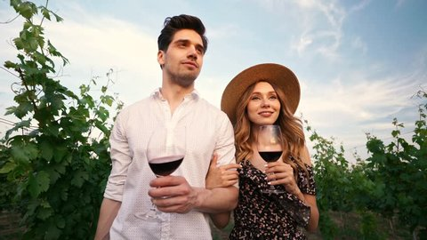 Young happy loving couple walking outdoors in the vineyard talking with each other drinking wine