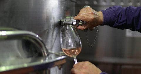 Person filling crystal glass with pink wine from tap of the stainless steel tank of wine production. Testing the quality of the drink. Routine check. Detail of hand, cup and tap. Mendoza. Argentina