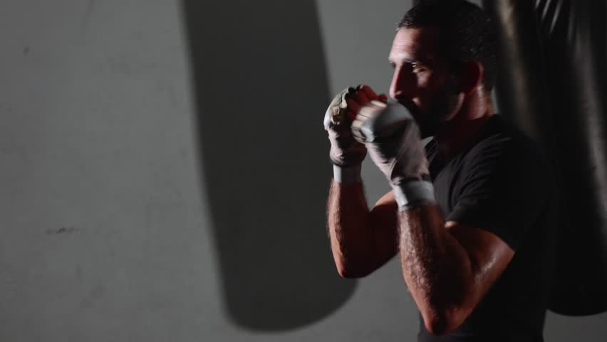 Male bearded boxer exercising shadow boxing. Fighter training punching in the darknes in slow motion.