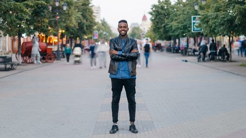 Zoom in time-lapse of happy African American guy wearing jeans and leather jacket standing alone in street downtown, smiling and looking at camera with crowd moving by.