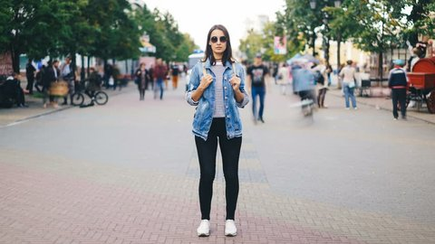 Zoom in time-lapse of female traveler standing in the street with backpack wearing sunglasses and casual clothing and looking at camera when men and women are rushing around.