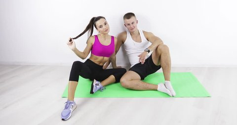Athletes are posing for the camera. Young brunette woman and man sitting on sport mat in the gym.