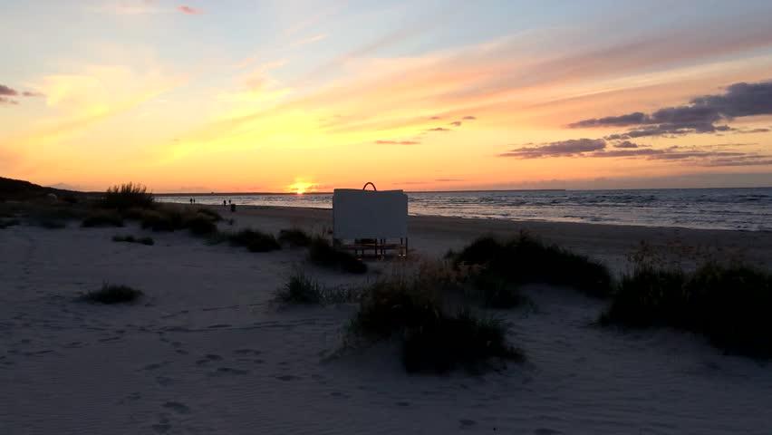 Sunset beach, sea, swimming people (silhouettes).  Waves, Baltic sea, sunset sky.