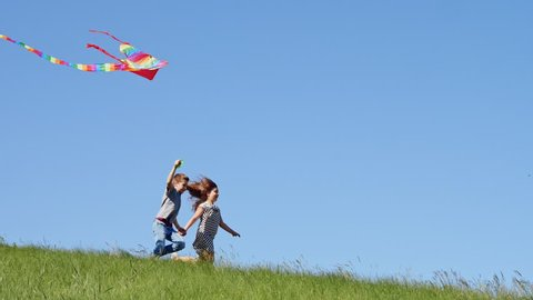 Happy childhood - Children run down the green hill with a flying kite at clear blue sky background.