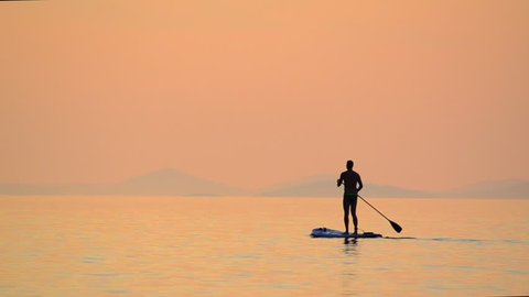 Sunset Silhouette of Man on Stand up paddle board surfing. Young man enjoing on Paddle-board on summer day. Paddling on the quiet sea at sunset. SUP