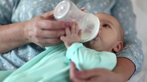 Grandmother feeds grandson from a bottle. Little baby boy on the hands of grandma. Three-month-old baby boy drinks milk, artificial feeding