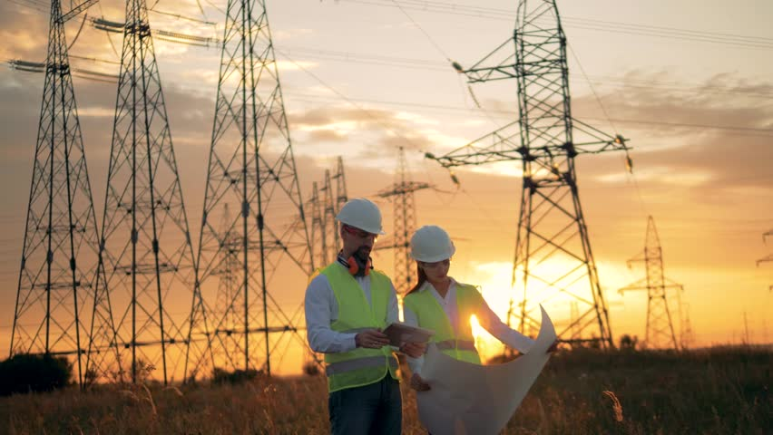 Two engineers in uniform work near power lines. Sunset background.