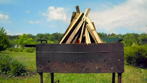 Beautiful red fire from slice wood, dark grey black coals inside metal brazier. Wood burning in the brazier on bright yellow fire. Flames fires preparation for cooking barbecue. Brazier on nature bbq.