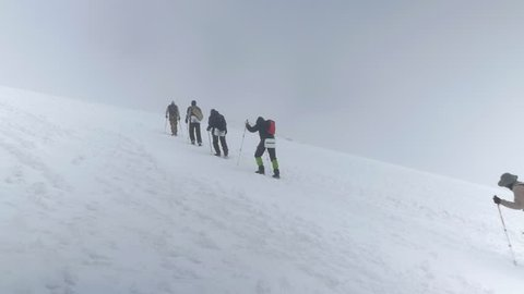 slow motion climbers group in chain goes up snowy mountain slope to Caucasus Mount Elbrus top against overcast sky