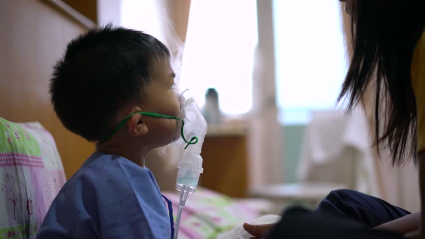 Sick Asian boy about 2 years and 8 months in hospital uniform using inhaler containing medicine with his mother help to stop coughing from disease like flu or RSV, Respiratory Syncytial Virus
