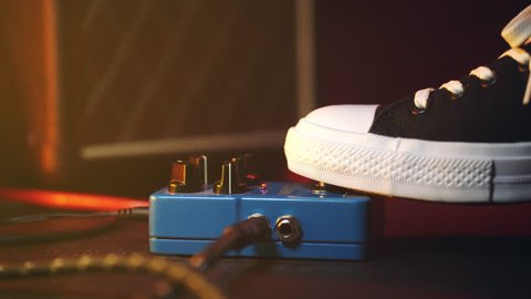 Close up of guitar player foot pressing pedal. Musician uses music effect loop machine. Man in trendy sneakers, his foot playing at stage during concert. Macro view.