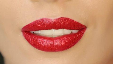 Closeup of a beautiful woman lips with beautiful makeup sending air kiss . Close up of girl's mouth having flirty emotions and sending air kiss .