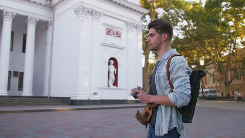 Attractive young handsome man tourist with backpack walking in city center and taking photos on vintage camera