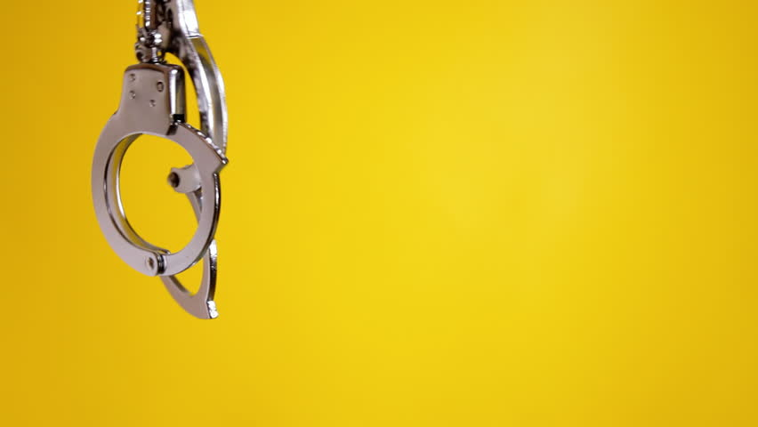 Shaking a pair of shiny metal handcuffs over a yellow background, room for copy-space on the right. Symbolic shot: crime, punishment, menace, fetish, sexuality, pleasure.