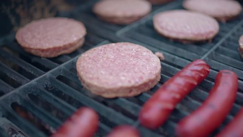 Close up of frozen hamburgers and hot dogs on a traditional barbecue