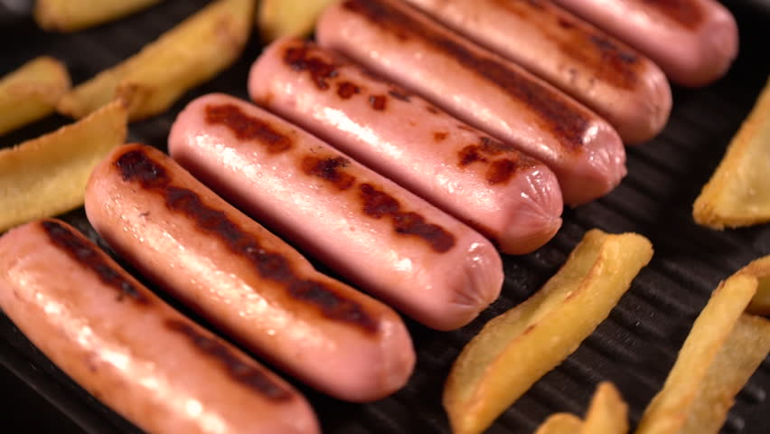 Sausages and potato wedges cooking on a grill or griddle in a rotating top down view   Shutterstock HD Video #1016638312