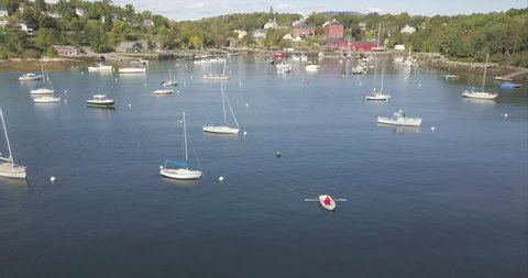Flying over a harbor full of boats, with a rowboat heading out to sea in Rockport, Maine.