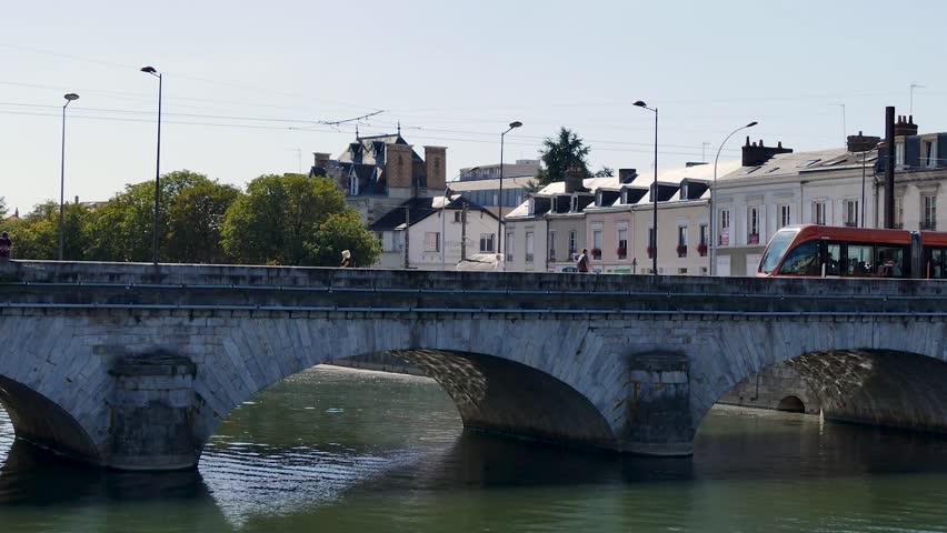 A tram passes through Le Mans, on a bridge over the Sarthe River. In 2015, the city had 143,325 inhabitants, making it the largest city in the Sarthe, the third largest city in the Pays de la Loire. | Shutterstock HD Video #1016683282