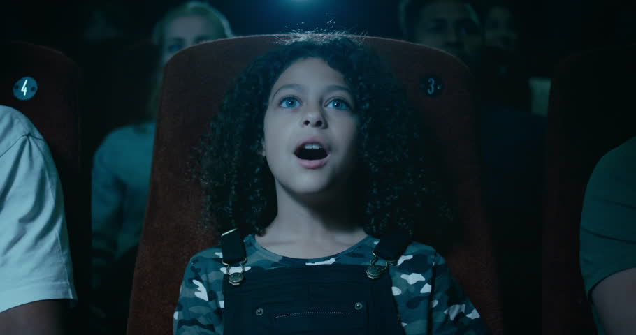 Captivated little girl in a movie theatre is awestruck by a incredible moment on screen | Shutterstock HD Video #1016706712