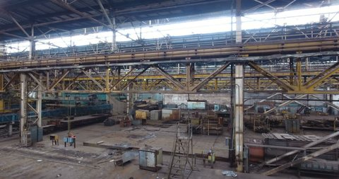Mykolaiv/Ukraine - YAN 12 2017: Aerial view in Non-working plant. Movement from above over metal structures and supporting beams in closed shop of old abandoned shipyard
