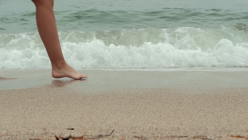 Legs of young woman going along ocean beach during sunrise. Girl stepping on wet sand of shoreline. | Shutterstock HD Video #1016726812