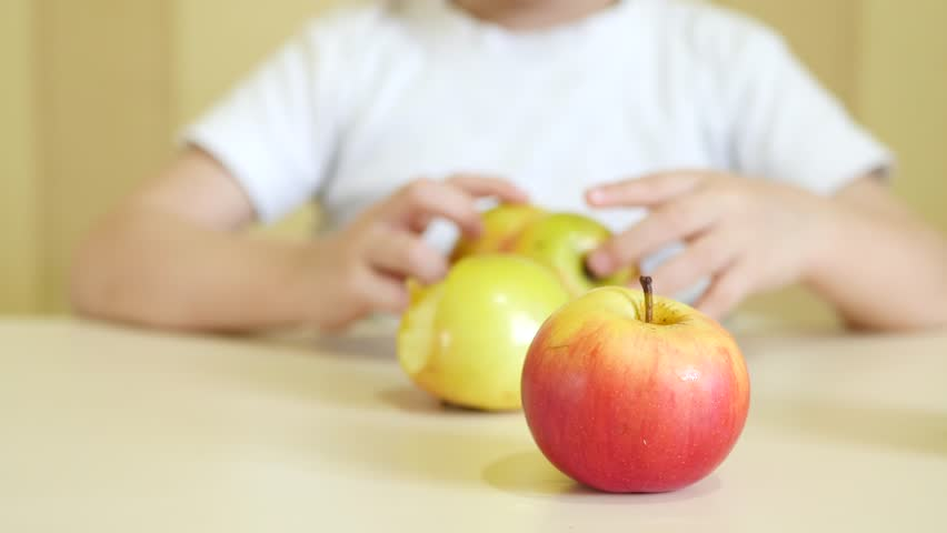 A child is playing with apples on the table. Close-up. The focus of the camera is aimed at apples.   Shutterstock HD Video #1016746672