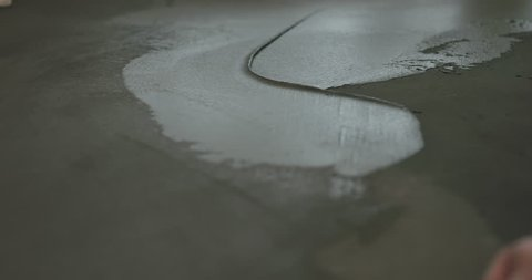 Slow motion closeup male worker applying micro concrete on the floor with a trowel