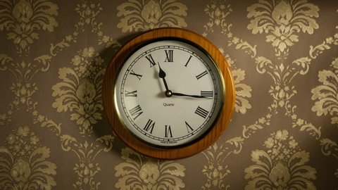 Time lapse clock - camera rotates with the big hand of a clock from 00:00 to 01:00, before and after that the camera stops.