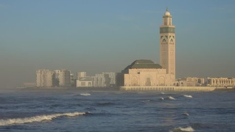Hassan II mosque in Casablanca and Atlantic ocean waves at sunset, Morocco, 4k
