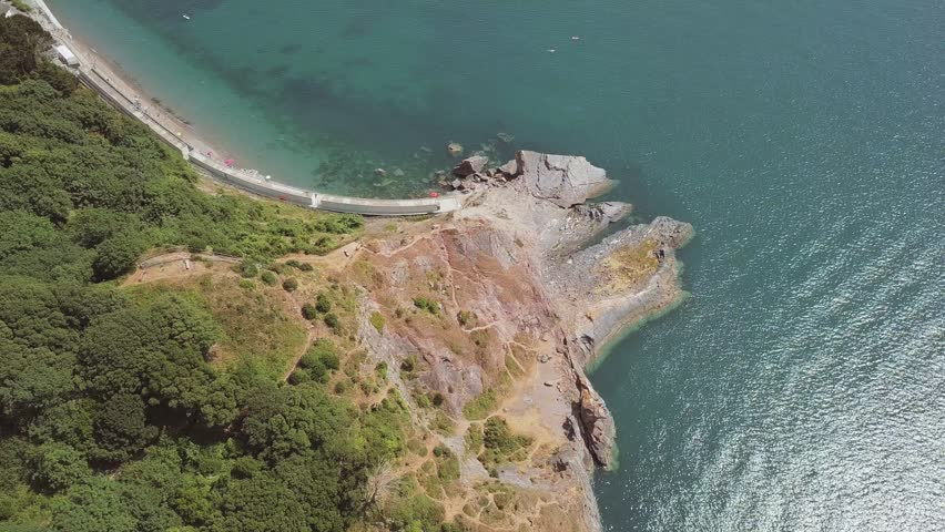 Overhead view of the beach in Torquay with its blue water and tall cliffs. Rock and woodland is visible from the sky.