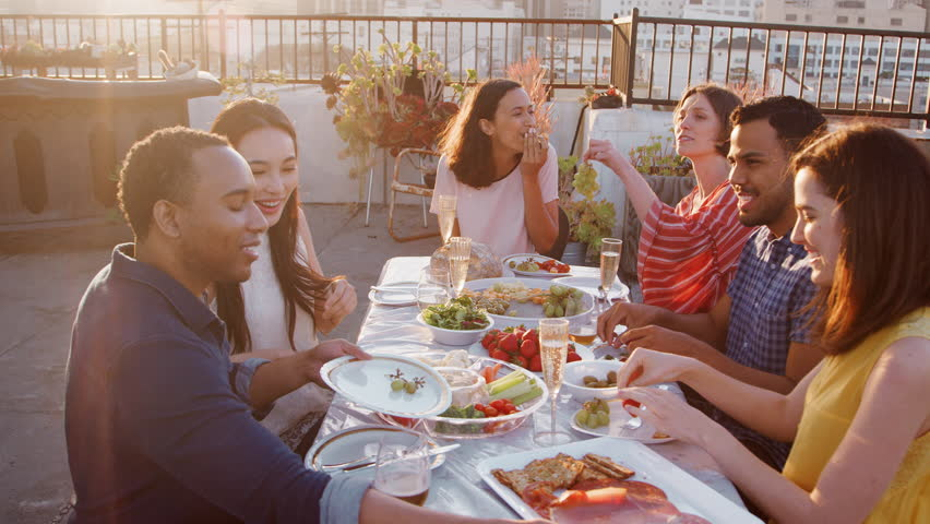 Friends Gathered On Rooftop Terrace For Meal With City Skyline In Background | Shutterstock HD Video #1016795242