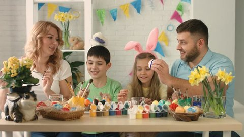 Funny family with kids wearing bunny ears painting eggs on Easter day