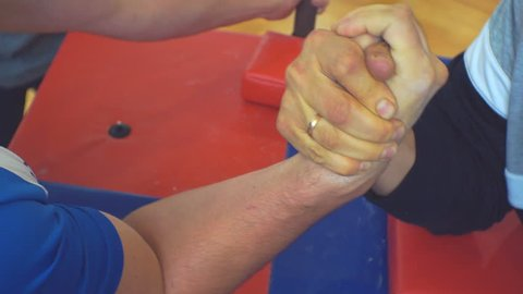 Two unrecognizable men arm wrestling. Concept of struggle, confrontation and heavy sport.