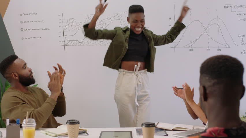 Black business people celebrating success corporate victory team leader woman excited dancing funny in boardroom presentation meeting