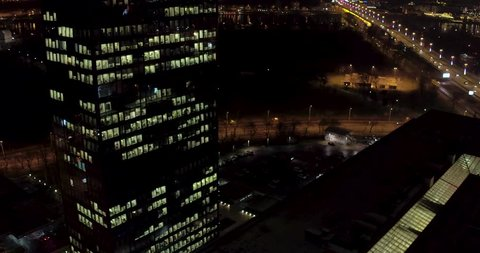 Night aerial view on skyscraper during holidays with decorated bridge in backround