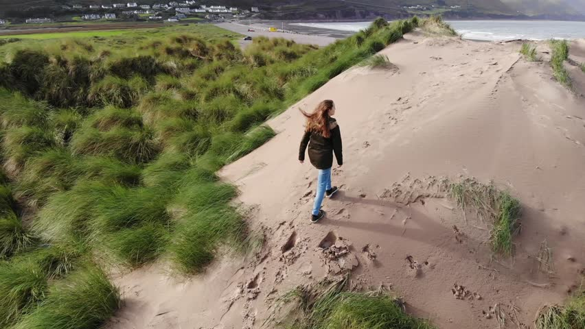Climbing on the sand dunes at the west coast of Ireland – aerial view | Shutterstock HD Video #1016875852