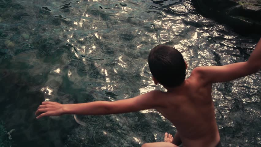 Happy boy is jumping into the sea water during summer holidays. Childhood and family life. Slow motion.