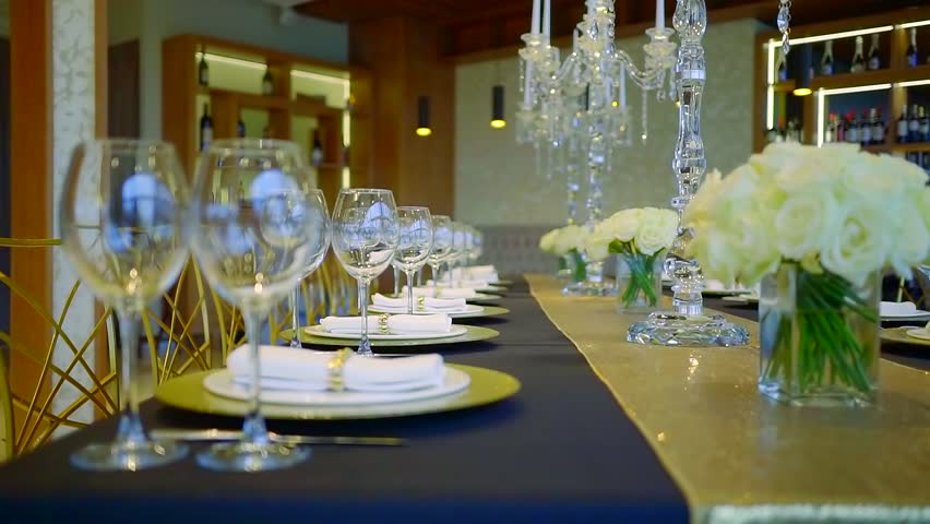 camera is moving along big table served for gala dinner in evening in luxury restaurant