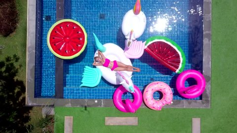 Top view of a woman in bikini suit on the unicorn floating rubbers. To enjoy the relax time in swimming pool on vacation at the hotel or resort