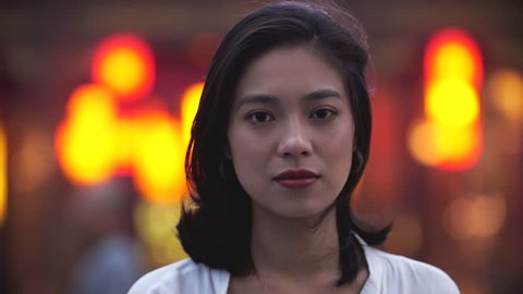 Close up of one lovely pretty young again girl smile at camera in the street with with blurred asian red lantern street at background 4k slow motion