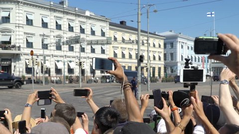 HELSINKI, FINLAND - JULY 16, 2018: A lot of people filming the motorcade Donald Trump on the streets of the city using smartphones. Meeting trump and Putin in Helsinki.