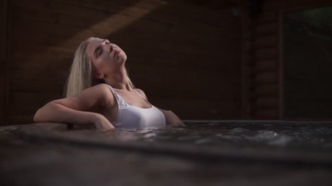 Sexy girl enjoying jacuzzi outdoors. Sexy woman enjoying spa outdoor. Blonde girl relaxing in jacuzzi poll. Spa procedures in hot pool outside