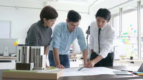 Architects team are working on paper blueprint and building model. Business woman suggest idea to designer. concept of construction, architecture, development and creative.