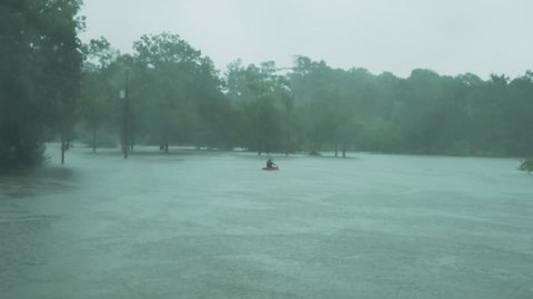 Kayaker seen Kayaking through a river during a light part of hurricane harvey. The water never is this high in this area. Footage taken in Houston texas during hurricane harvey.